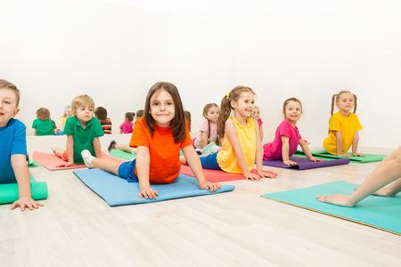 Kids stretching backs on yoga mats in sports club Stock Photo - 81373305