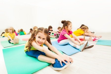 Beautiful girl stretching legs with friends in gym Stok Fotoğraf