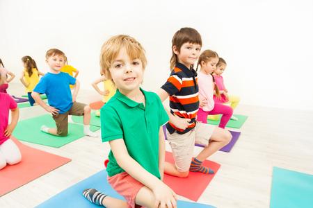 Happy kids practicing gymnastics on mats in gym