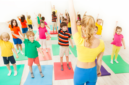 Kids doing gymnastic exercises with female coach