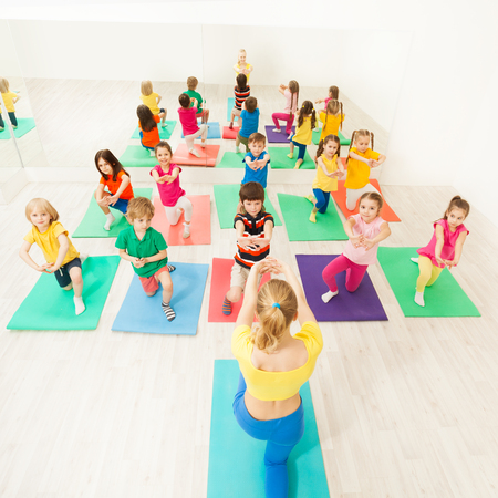 Happy kids doing kneeling exercises in gym