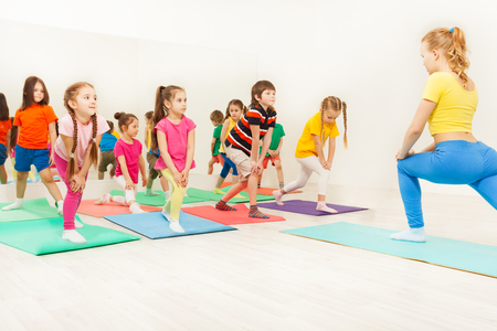 Kids doing gymnastic exercises in fitness class Stock Photo