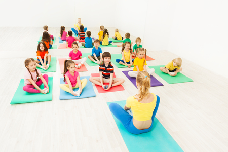 Female instructor giving yoga class for kids