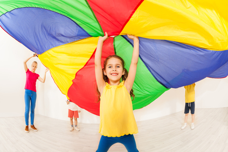 Happy girl waving parachute during sports festival Banque d'images