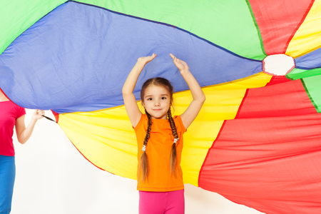 Girl standing under parti-colored parachute canopy