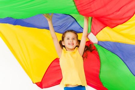 Joyful girl jumping under canopy made of parachute