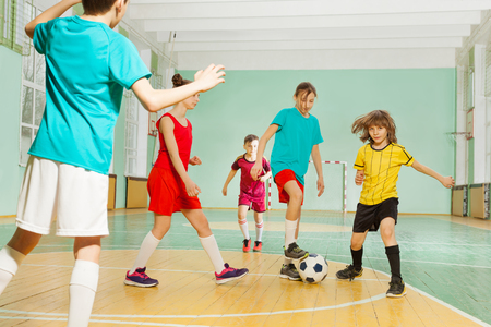 Children playing football in school sports hall