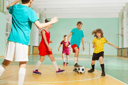 Bambini che giocano a calcio nel palazzetto dello sport della scuola Archivio Fotografico - 81339925