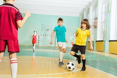 Boy striking ball playing football in sports hall