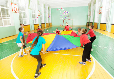 Children playing parachute games in sports hall