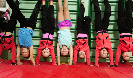Sporty kids making handstand position in gym