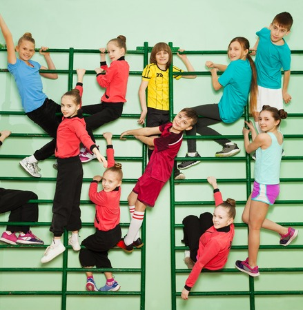Happy kids exercising on wall-mounted gym ladder