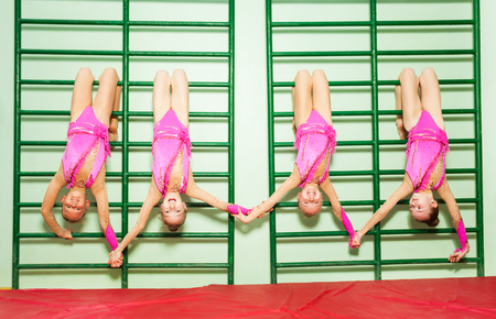 Young gymnasts hanging upside down from wall bars