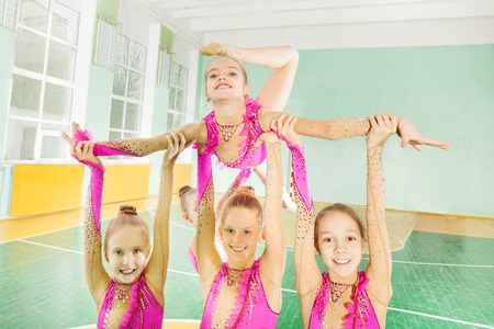 Happy girls doing routine in rhythmic gymnastics