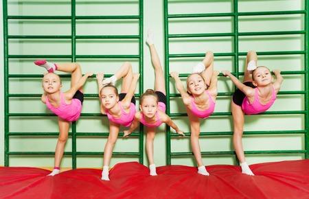 Meisjes trainen gymnastiek in de buurt van de muur gemonteerde ladder