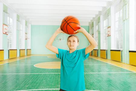Sporty girl tossing ball in basketball rim