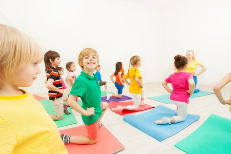 Cute kid boy practicing gymnastics in gym Stock Photo