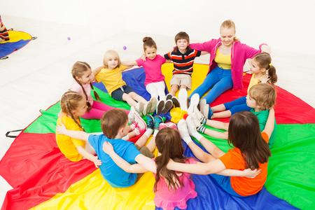 Gelukkige kinderen die cirkelspellen spelen met leraar