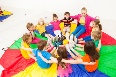 Happy children playing circle games with teacher Banco de Imagens