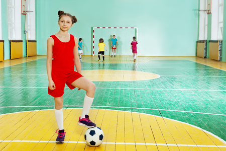 Sporty girl standing with soccer ball in futsal