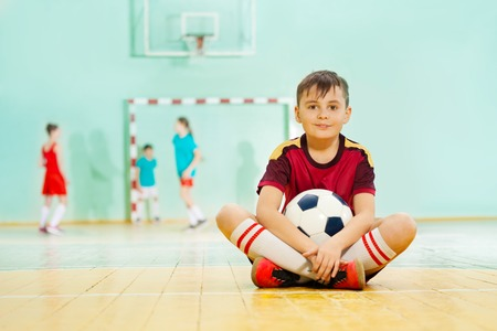 Happy boy sitting on the floor with soccer ball