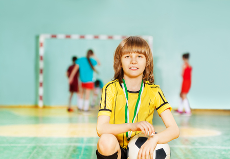 Happy boy sitting with soccer ball in sports hall