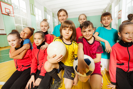 Childrens soccer team having fun together in gym Zdjęcie Seryjne