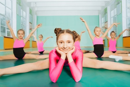 Meisje zit in splitsingen tijdens de gymnastiek klasse Stockfoto