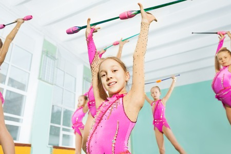 happy girl doing gymnastic exercises with clubs Stock Photo