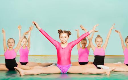 女の子が体操の授業中に分割を実行します。