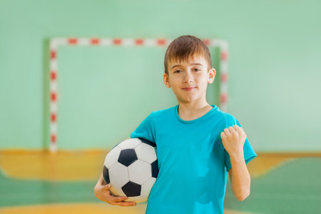 Happy boy, football winner, holding soccer ball Banco de Imagens