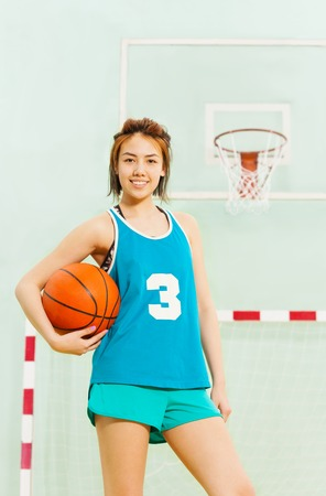 Teenage basketball player with ball under her arm