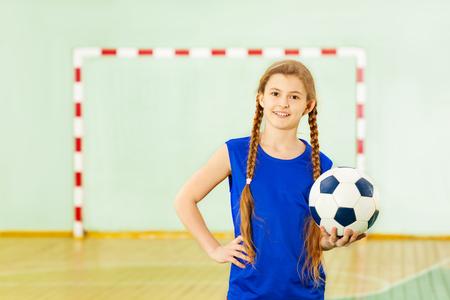 Tiener met voetbalbal in schoolgymnastiek Stockfoto
