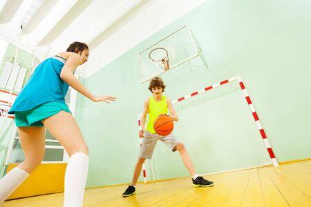 Teenage boy dribbling basketball during the match
