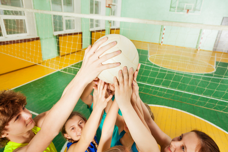 Teenage volleyball team players serving a ball