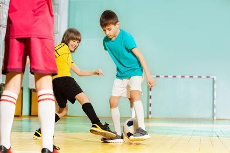 Happy boys playing football in school sports hall