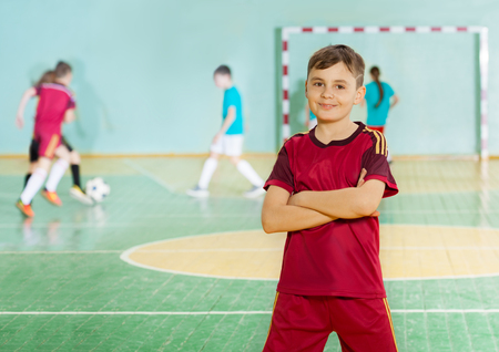 Preteen football player standing in sports hall