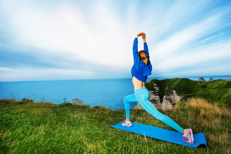 Sporty woman exercising on the top of cliffs Stock Photo