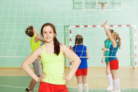 Girl standing next to the volleyball net in gym 스톡 콘텐츠