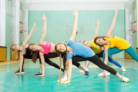 Chicas haciendo ejercicios de estiramiento en el pabellón de deportes Foto de archivo - 82009994