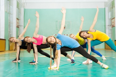 Girls doing stretching exercises in sports hall