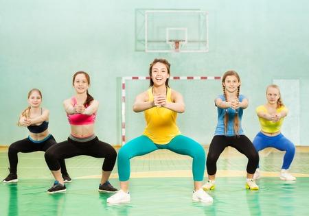 Sporty teenage girls making squats in school gym Foto de archivo