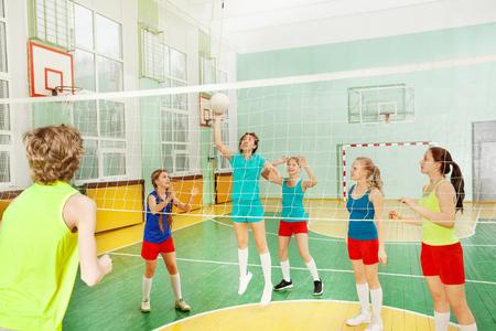 Tienermeisje die de bal dienen tijdens volleyballgelijke