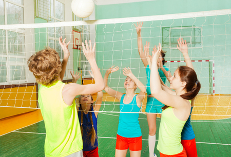 Tieners spelen volleybal in gymnasium van de school Stockfoto