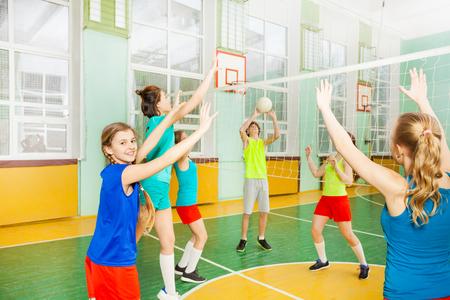 Tienervolleyballers die in gymnastiek matchen Stockfoto - 81965174