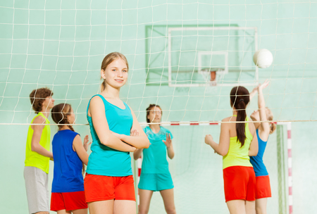 Sonriente niña de pie junto a la red de voleibol Foto de archivo - 82009983