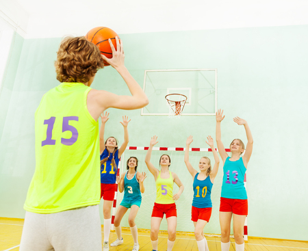 Basketball team defending hoop from another player Stock Photo