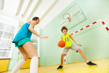 Teenage boy and girl playing basketball in gym