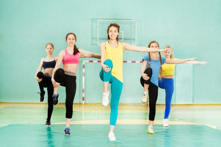 Girls holding balance during knee-to-chest stretch