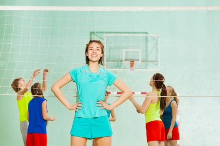 Portrait of Asian teenage girl standing next to the volleyball net with arms at hips during training Imagens